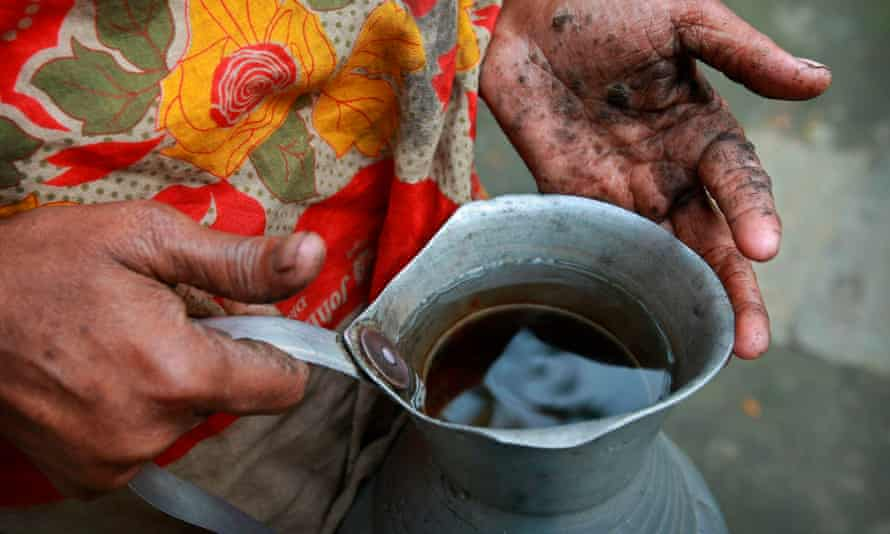 Hanufa Bibi, 45, holds a vessel of contaminated water from a well in her village in Chandipur, about 120km east of Dhaka, in Bangladesh.