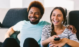 Happy young couple watching TV