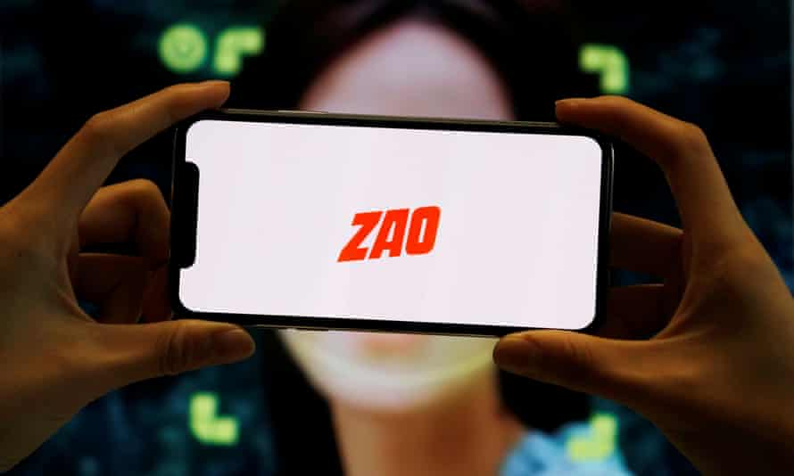 A person holds a phone showing the Zao app's logo