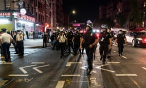 Police watch as hundreds of people protest in New York.