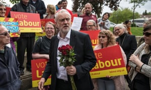 Jeremy Corbyn holds red roses given to him by activists and supporters as he visited a local shopping arcade in Oxford.