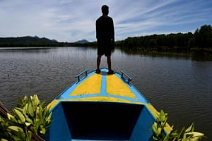 A student heads out on a boat to plant mangroves in Calang, Indonesia