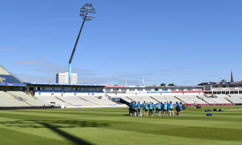 England gather in a circle on the Edgbaston outfield with empty stands behind them.