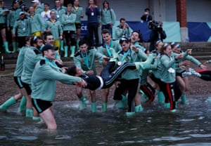 Cambridge men's Cox Hugo Ramambason is thrown in the river as they celebrate winning the boat race.