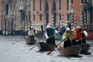 Venice, Italy: men dressed as La Befana, an imaginary elderly woman who is thought to bring gifts to children during the festival of Epiphany, row boats down the Grand Canal