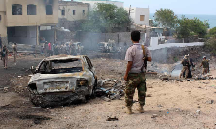 Yemeni loyalist forces and onlookers gather at the scene of a suicide attack targeting the police chief in the base of the Saudi-backed government on April 28, 2016 in Yemen's second city Aden.