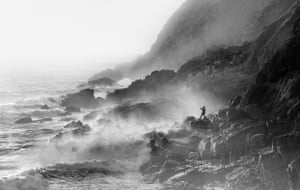 Fisherman on rocks in strong westerly winds, Porth Nanven, Cornwall