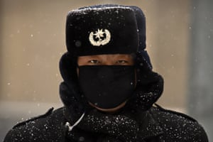 Beijing, China Snow settles on a security guard's uniform as he stands outside an office building