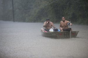 Two men attempt to rescue a family trapped by floodwaters Thursday near Patton Village, Texas.