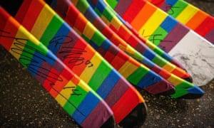 A close up shot of pride tape wrapped around ice hockey sticks.