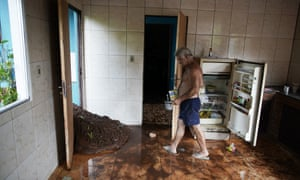 Darcy Brum walks past mud that entered in the kitchen of the house of his father-in-law near Brumadinho, Brazil