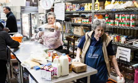 NEW YORK, NY - November 23rd, 2015: Milagros Feliciano, left, and Zoila Estrella, right, volunteers at the West Side Campaign Against Hunger, check recipients out in the food pantry on Monday morning. CREDIT: Alex Welsh for The Guardian