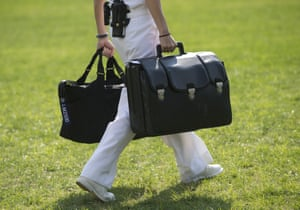 A White House military aide carries a briefcase known as the 'football', containing emergency nuclear weapon codes