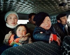 A family evacuating during a snowstorm, near Tsengel village.