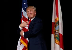 The Republican presidential candidate, Donald Trump, hugs the US flag during a rally in Tampa, Florida