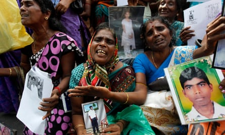 Tamil women cry as they hold up images of their disappeared family members during the country's civil war.