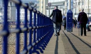 Older people walk along the beachfront promenade in Eastbourne