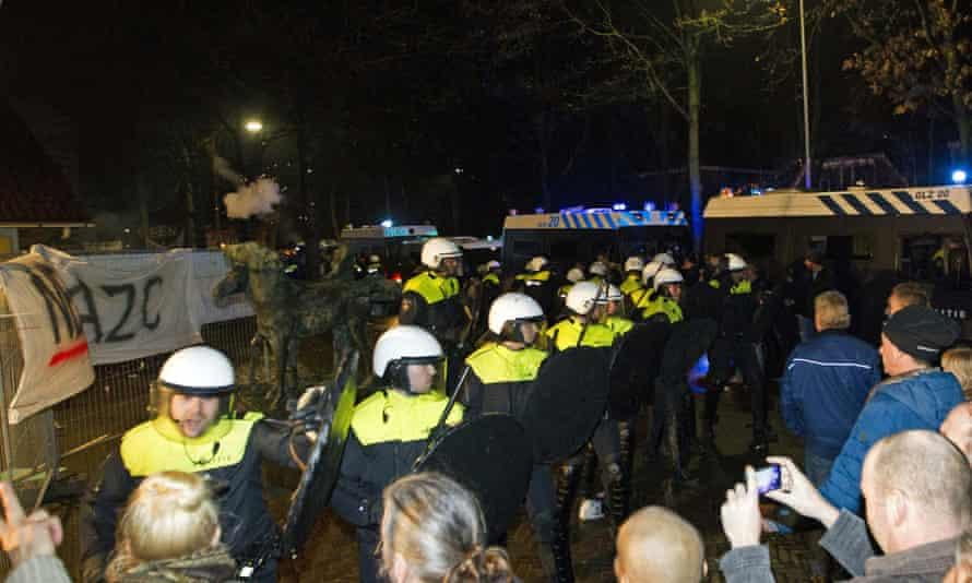 Police forces stand in front of protestors during a demonstration on December 16, 2015 at a council meeting about plans to open a refugee centre for 1500 refugees in Geldermalsen.