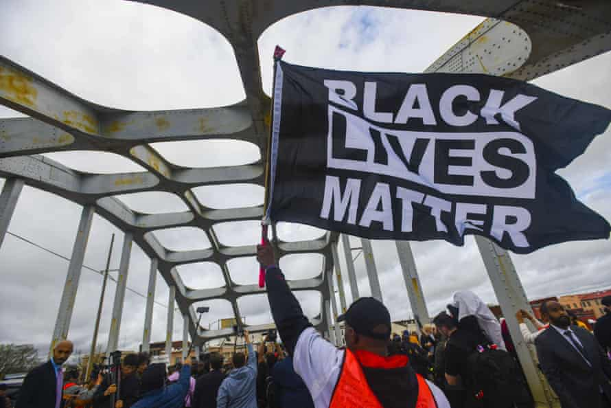 A Black Lives Matter demonstrator waves a flag on the Edmund Pettus Bridge during the Bloody Sunday commemoration in Selma, Alabama, in March.