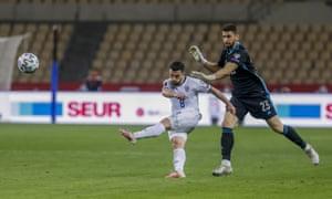 Kosovo's Besar Halimi, left, kicks the ball and scores his team first goal next to Spain's goalkeeper Unai Simon.