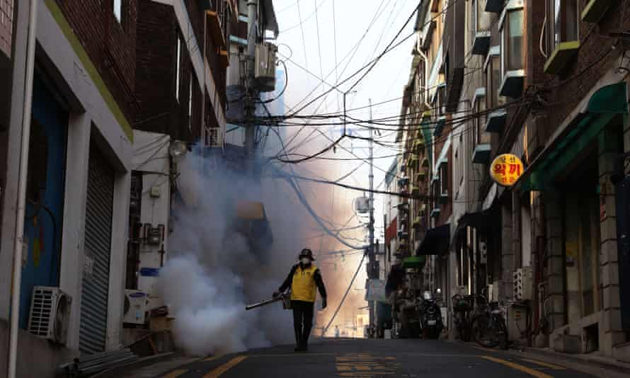 A man disinfects a street in Seoul, South Korea, on 18 March 2020: 'South Korea has been effective in controlling its mortality rate through widespread rigorous measures.'