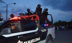 Policemen take part in a police operation to regain control of a prison in Ciudad Victoria.