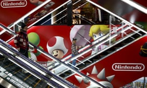 People ride escalators past an advertisement of the Nintendo Co videogame maker in Tokyo, Japan.