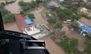 Flood victims, including a patient needing kidney dialysis, await an airlift from a rooftop in Abiyana village, Gujarat.