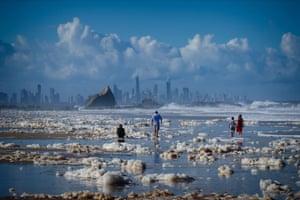 People walk through foam on Currumbin Beach on the Gold Coast, Australia