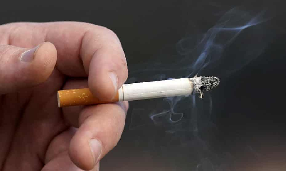 A man holding a lit cigarette