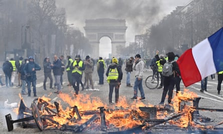 Gilets jaunes protesters setup a barricade with fire on the Champs-Élysées during the 18th consecutive Saturday national protest