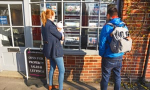 couple looking through estate agent window