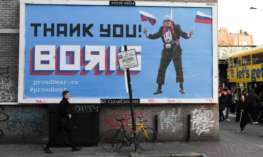 Man walks past a billboard depicting Boris Johnson waving Russian national flags reading 'Thank you Boris'.
