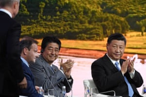 Japan's Prime Minister Shinzo Abe (middle) and China's President Xi Jinping (right) applaud Vladimir Putin's speech