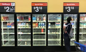A woman looks over bare refrigerator shelves in a Walmart store in Houston, Texas, on Friday.