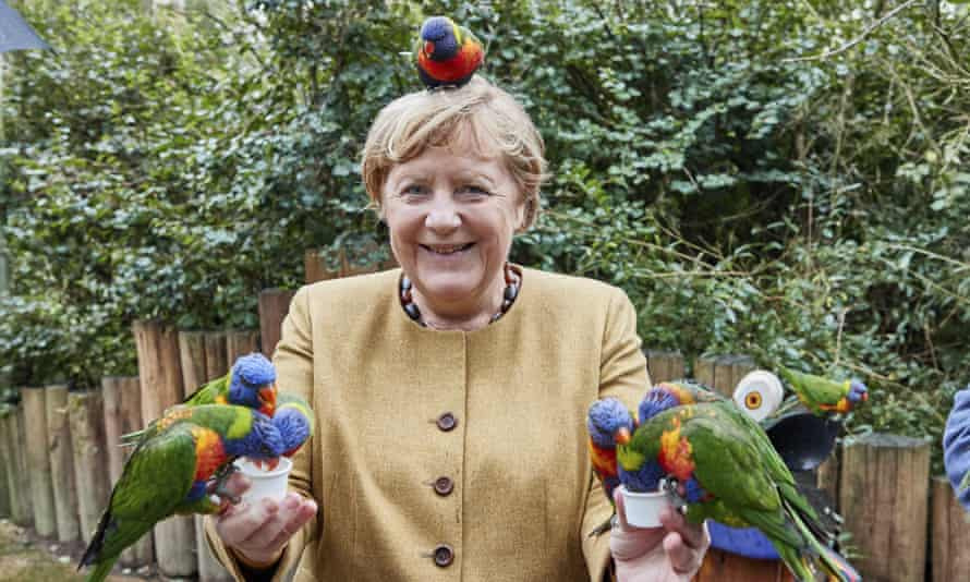 German Chancellor Angela Merkel feeds Australian lorikeets at Marlow Bird Park in Marlow, Germany.