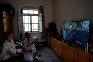 Residents watch on television as the president, Xi Jinping, reviews troops at the military parade
