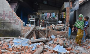 A woman walks past debris from a collapsed wall in Lendang Bajur on Lombok island.