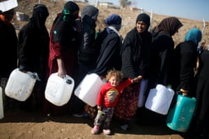 Iraqis, who fled Mosul from Isis, wait in line for cooking and lighting fuel at the Khazer camp.