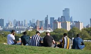 People enjoy the sunshine on Primrose Hill, London.