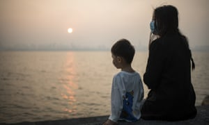 A woman and child watch the sunset by the Donghu Lake in Wuhan, central China's Hubei Province, 5 May 2020.