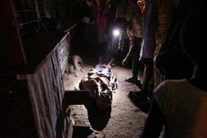 Mathare residents gather and shine a torch on the body of James Mureithi, who they say was shot twice, once in the legs and once in the chest