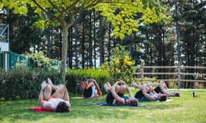 An outdoor yoga class, people lying on their backs