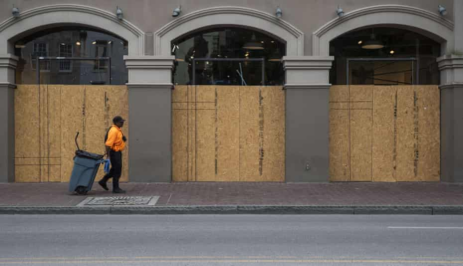A worker walks past a boarded up store in New Orleans, Louisiana, U.S., on Wednesday, April 8, 2020. On Wednesday, Louisiana reported 17,030 Covid-19 cases and 652 deaths, according to the Louisiana Department of Health.