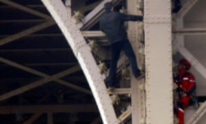 An unidentified man climbs the Eiffel Tower in Paris, next to a rescuer dressed in red