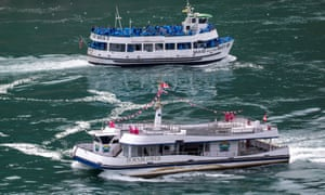 American tourist boat glides past a Canadian vessel limited to just six passengers in Niagara Falls American tourist boat Maid Of The Mist, limited to 50 % occupancy under New York state's rules amid the spread of the coronavirus disease, on Tuesday in Niagara Falls, Ontario, Canada.