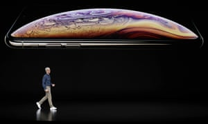 Apple's CEO, Tim Cook, appears on stage in front of an image of the recently released iPhone XS.