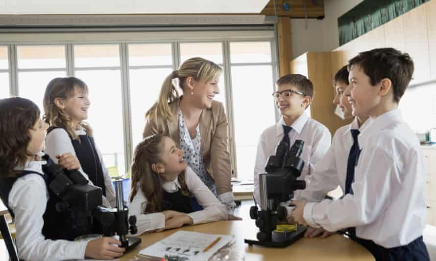 Happy students and teacher using microscopes in classroom