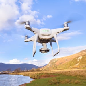 A drone flying over hills and a lake