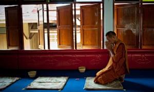A monk prays in a Buddhist temple in Ayutthaya, Thailand.